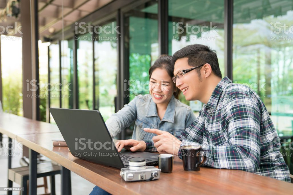 Happy asian couple using laptop spending time together at coffee shop,family concept. stock photo