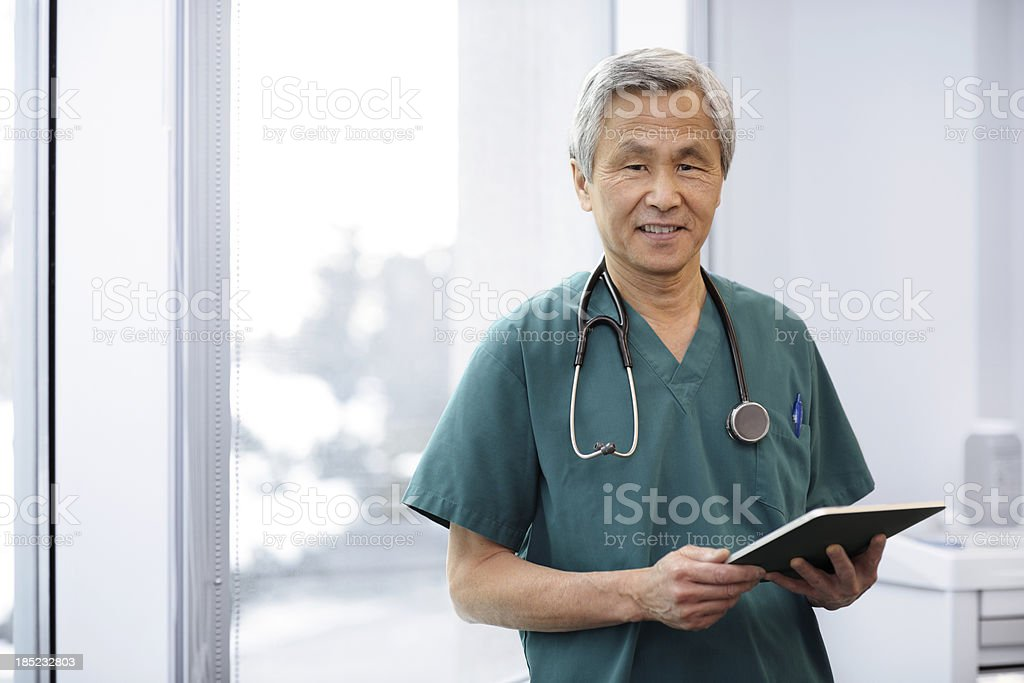 Happy Asian Doctor using a Tablet stock photo