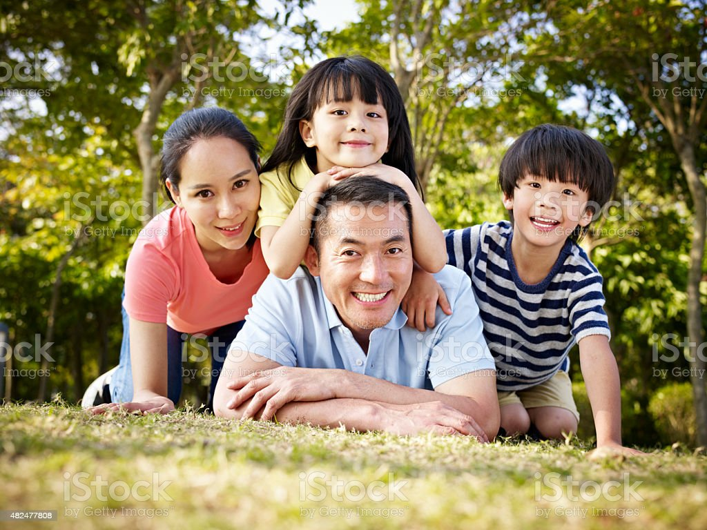 happy asian family outdoors in park stock photo