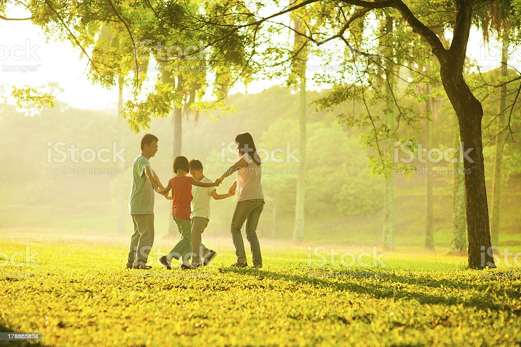 Happy asian family playing on the field stock photo
