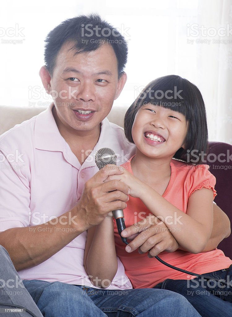 Happy Asian family singing karaoke royalty-free stock photo