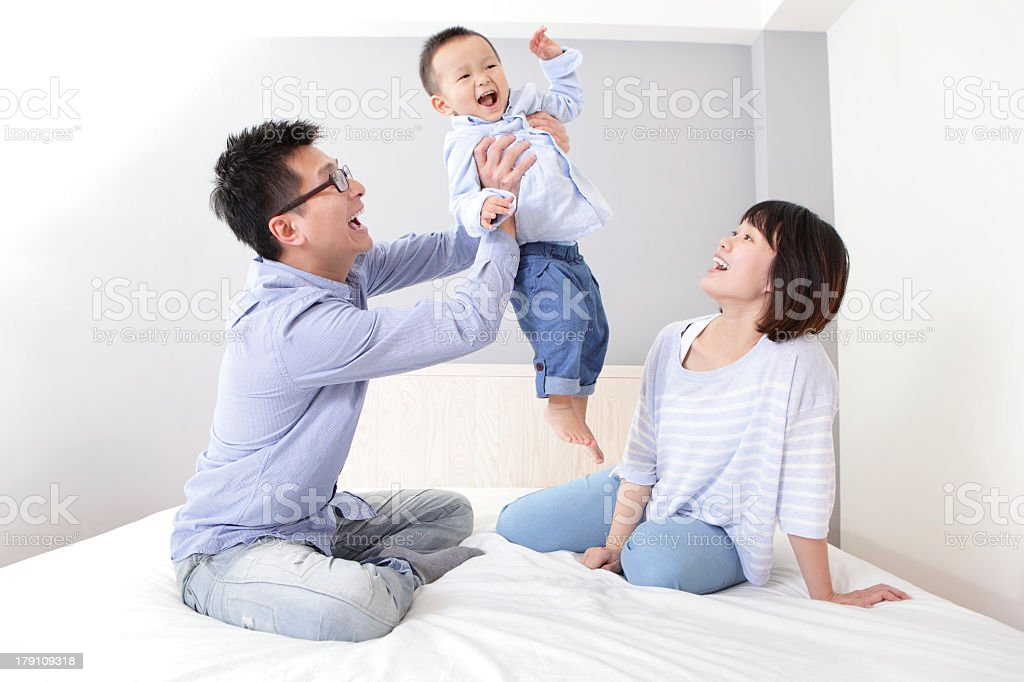 Happy Asian family sitting on a bed and playing together stock photo