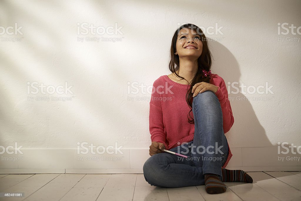Happy Asian girl holding pregnancy test at home stock photo