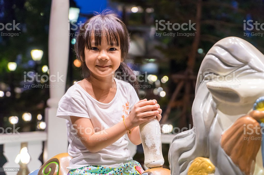 happy Asian girl riding on a horse merry go round. stock photo