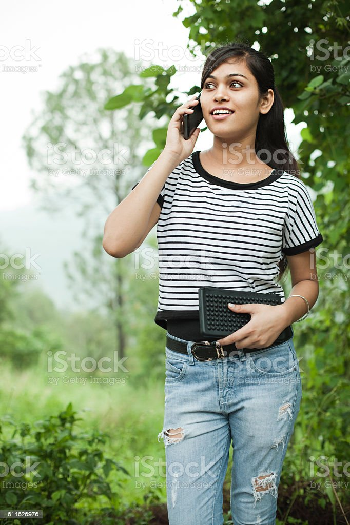 Happy Asian girl talking on smart phone outdoor in nature. stock photo