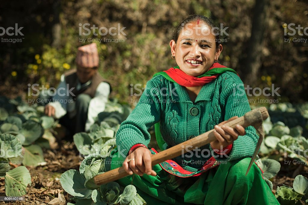 Happy Asian peasant woman in farm with hook. stock photo