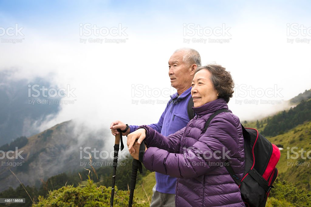 happy asian senior couple hiking on the mountain stock photo