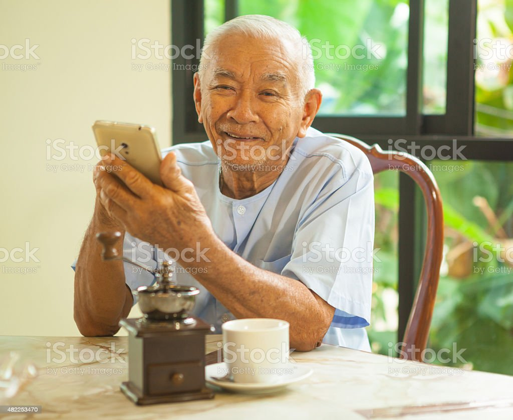 Happy asian senior man using the mobile phone in home stock photo