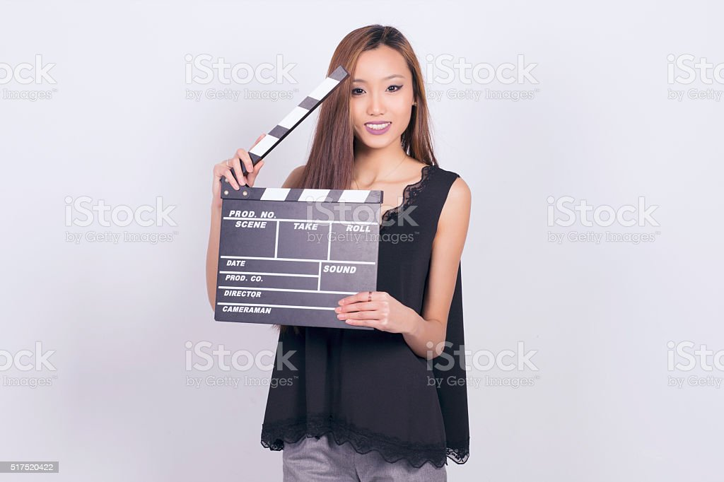Happy asian woman holding a cinema clapper board. stock photo