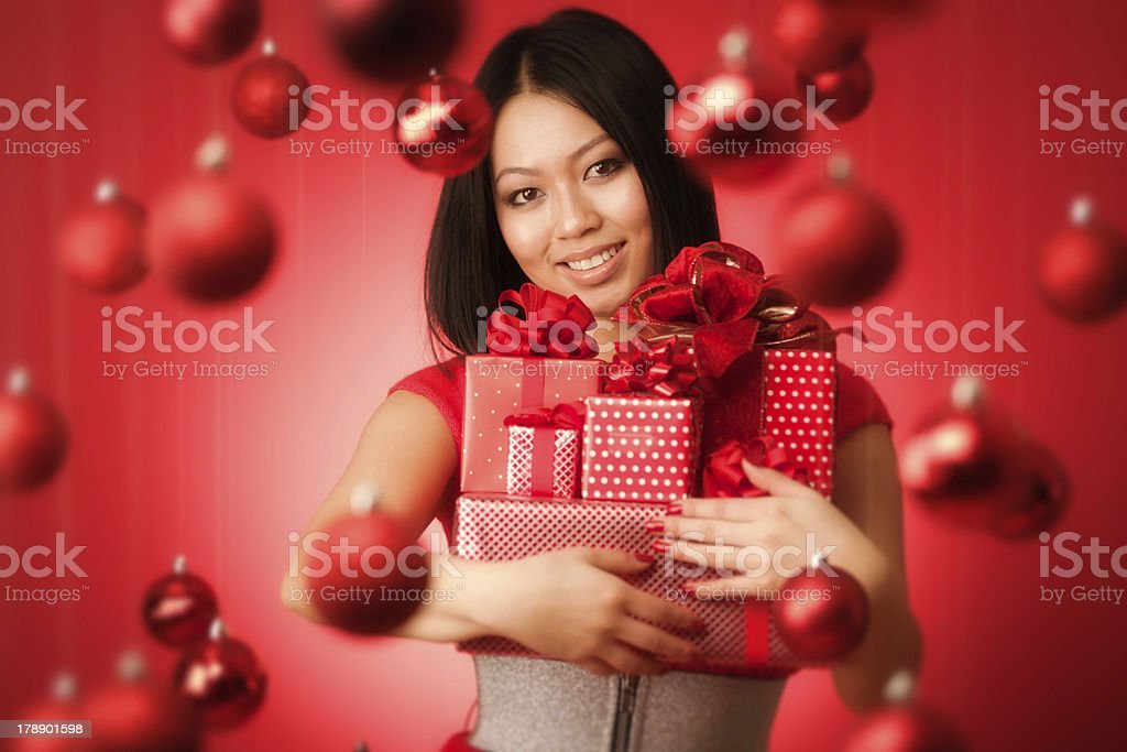 Happy Asian Woman Holding Gifts with Red Christmas Background Hz royalty-free stock photo