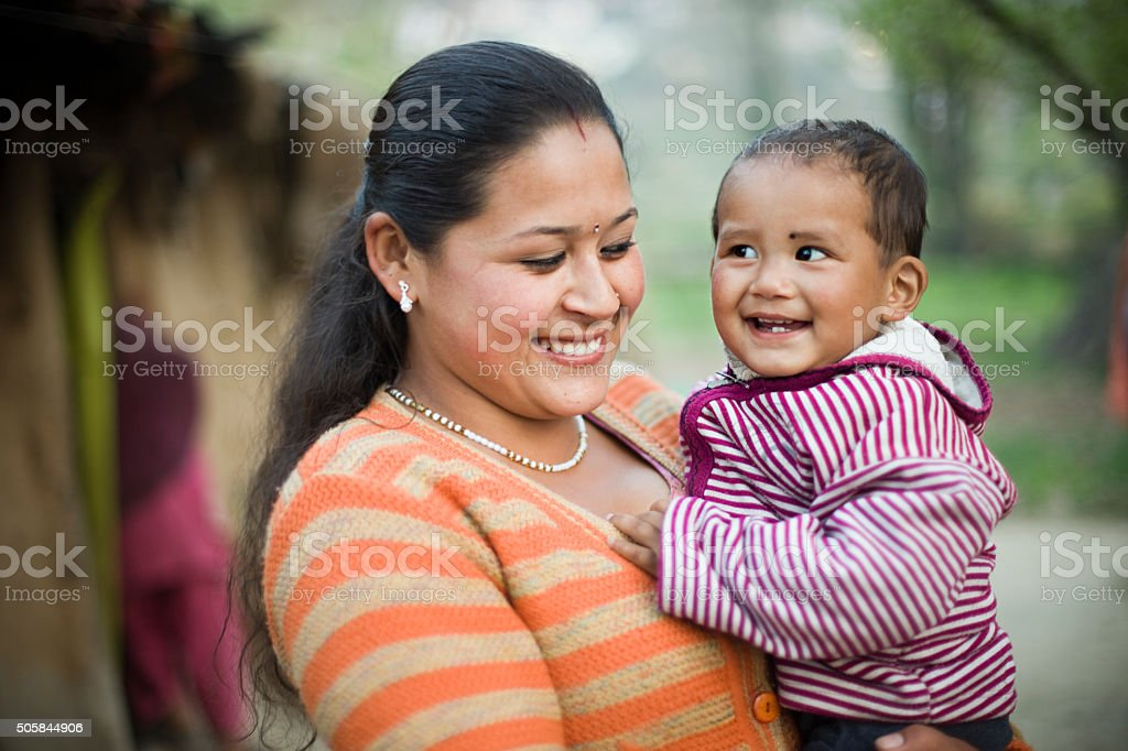 Happy Asian woman lifting up her child in arms. stock photo