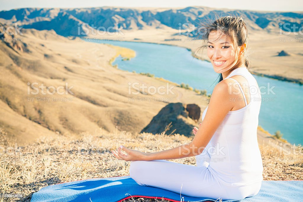 Happy asian woman relaxing and meditating above river valley stock photo