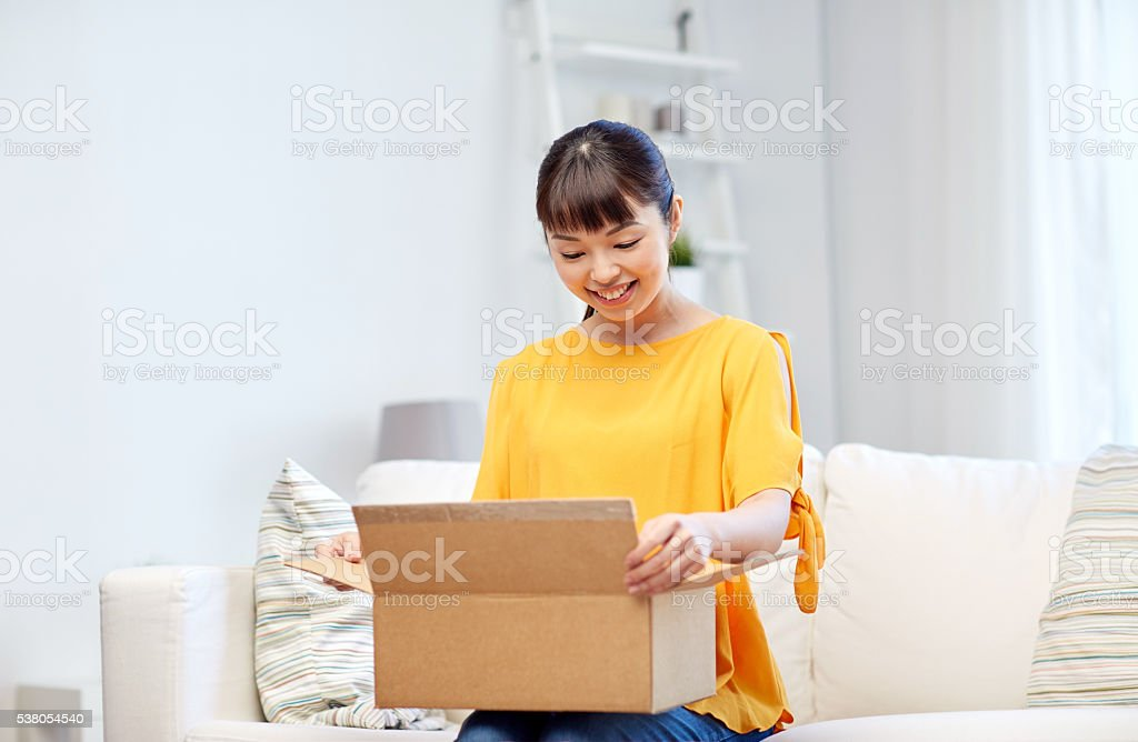 happy asian young woman with parcel box at home stock photo
