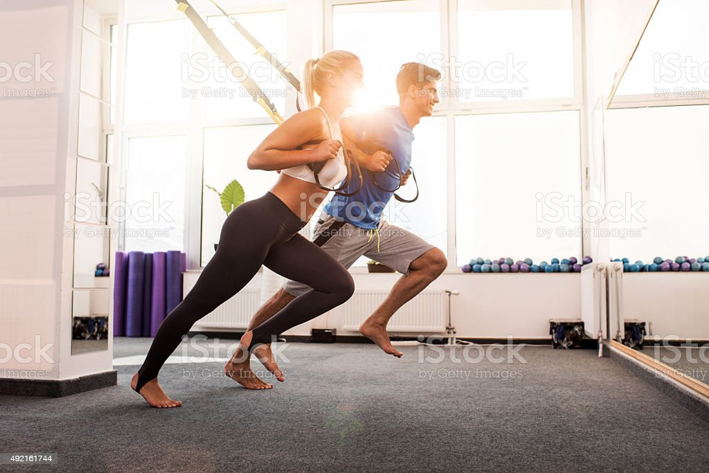 Happy athletes doing stretching exercises on Pilates equipment. stock photo