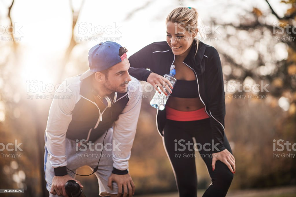 Happy athletes taking a break from exercising in nature. stock photo