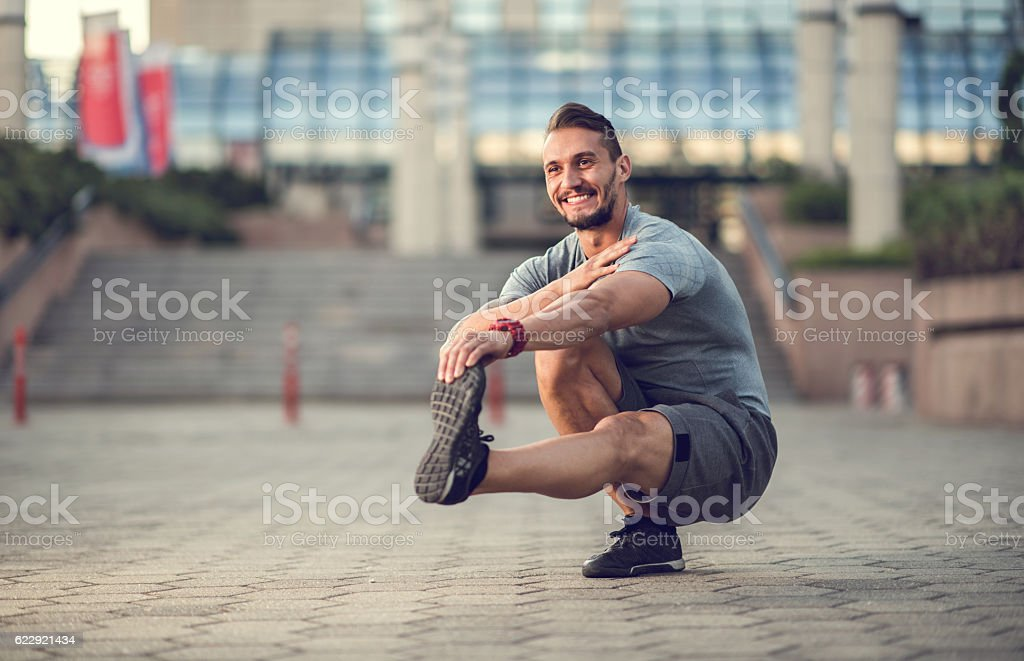 Happy athletic man stretching his leg while crouching outdoors. stock photo