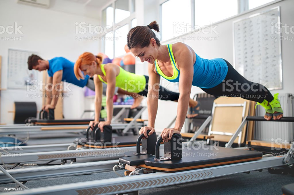 Happy athletic people exercising on Pilates machines in a gym. stock photo