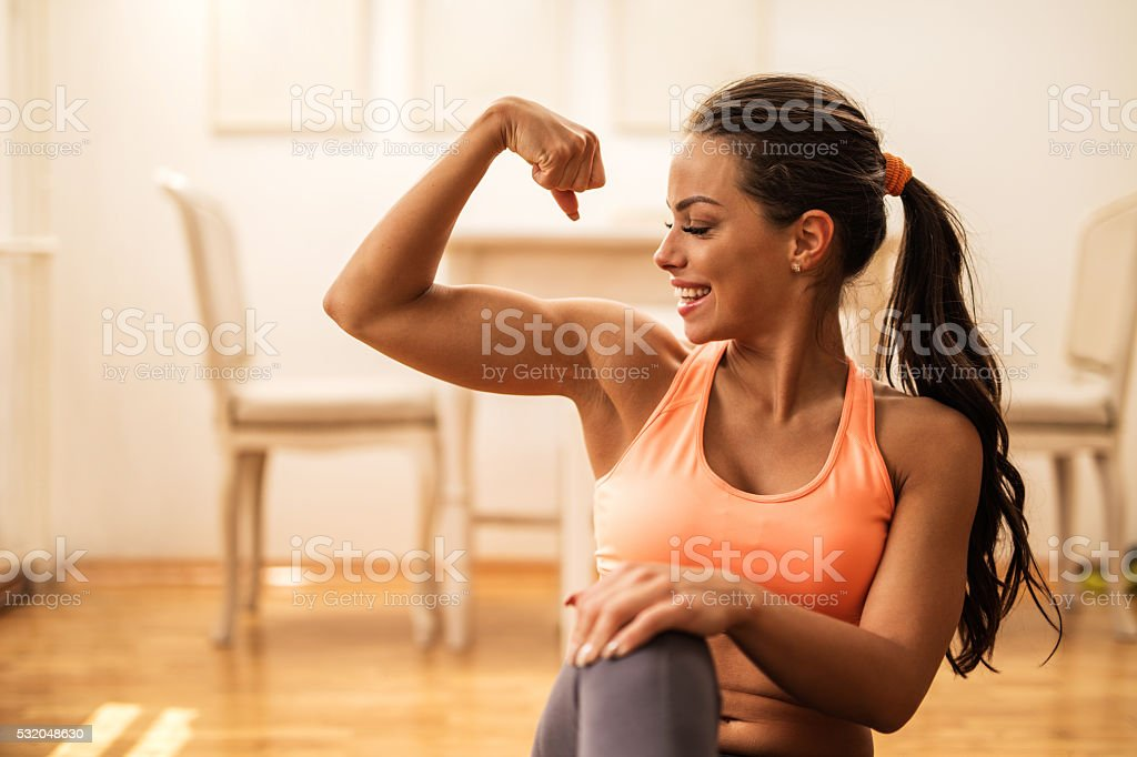 Happy athletic woman flexing her bicep at home. stock photo