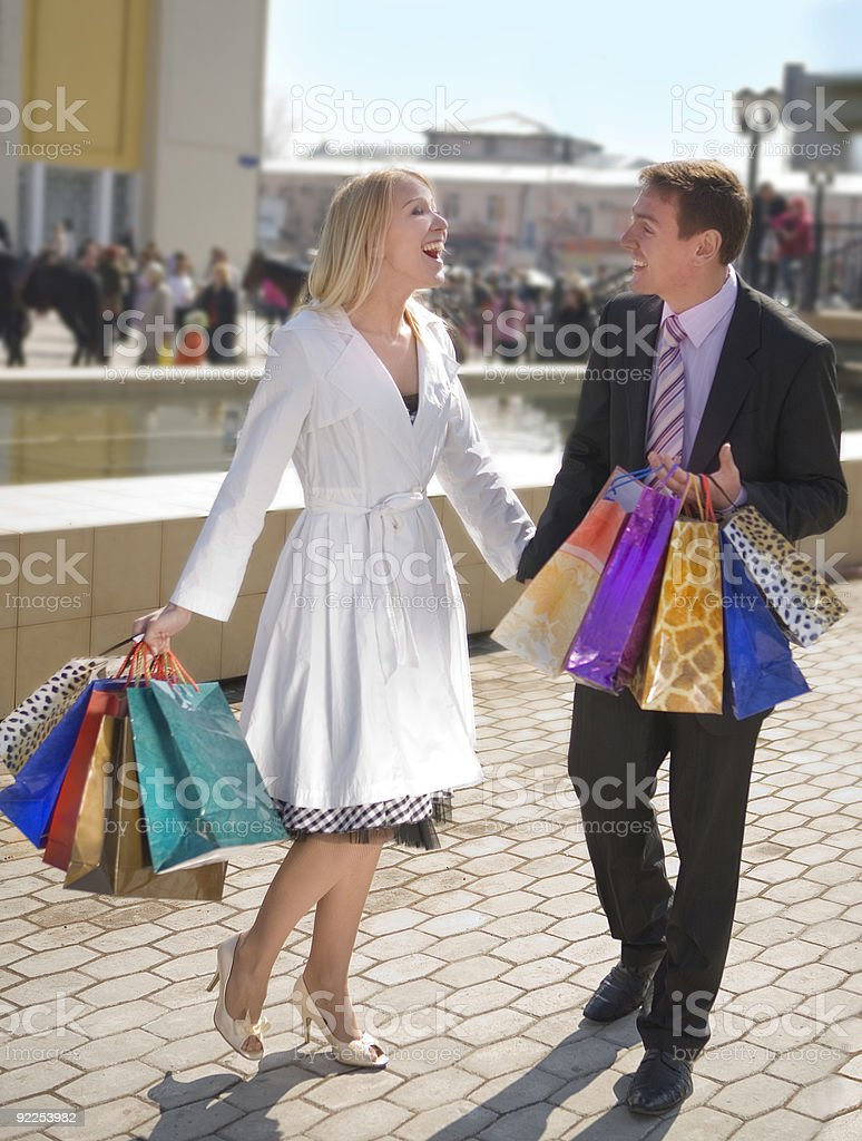 Happy attractive couple with shopping bags in the street. royalty-free stock photo
