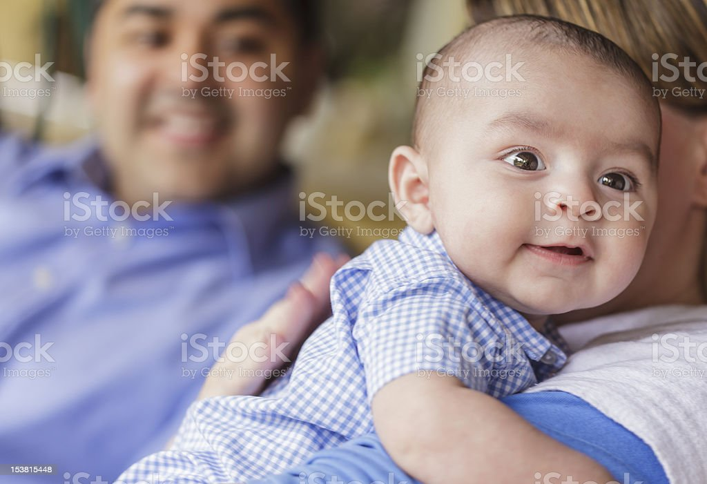 Happy Attractive Mixed Race Couple Burping Their Son stock photo