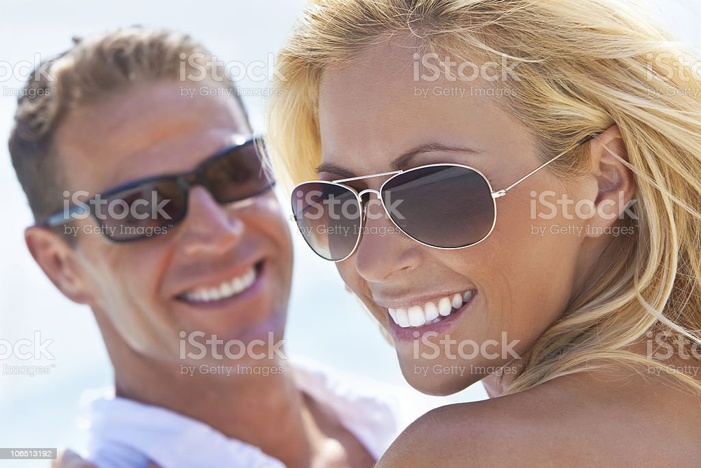 Happy Attractive Woman and Man Couple In Sunglasses At Beach stock photo