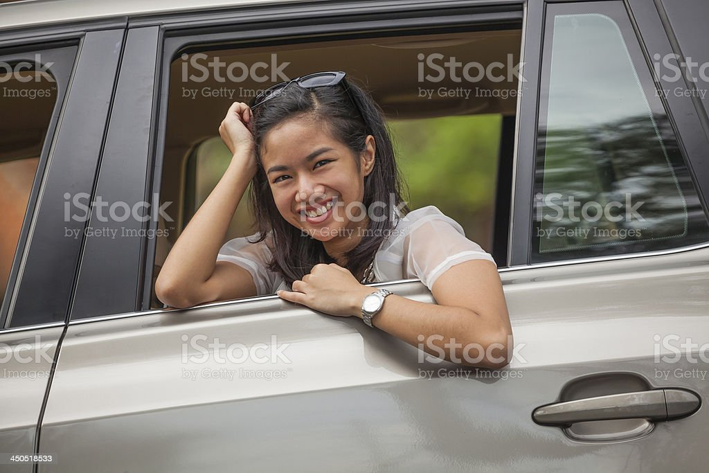 Happy attractive woman sitting in car and looking out stock photo