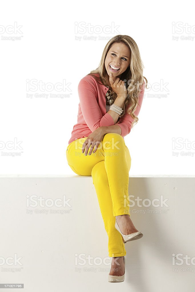 Happy attractive woman sitting on the ledge of a wall stock photo