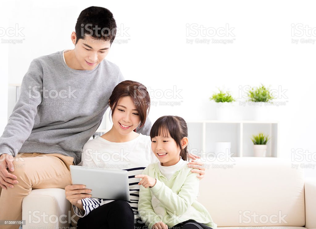Happy Attractive Young  Family watching the tablet stock photo