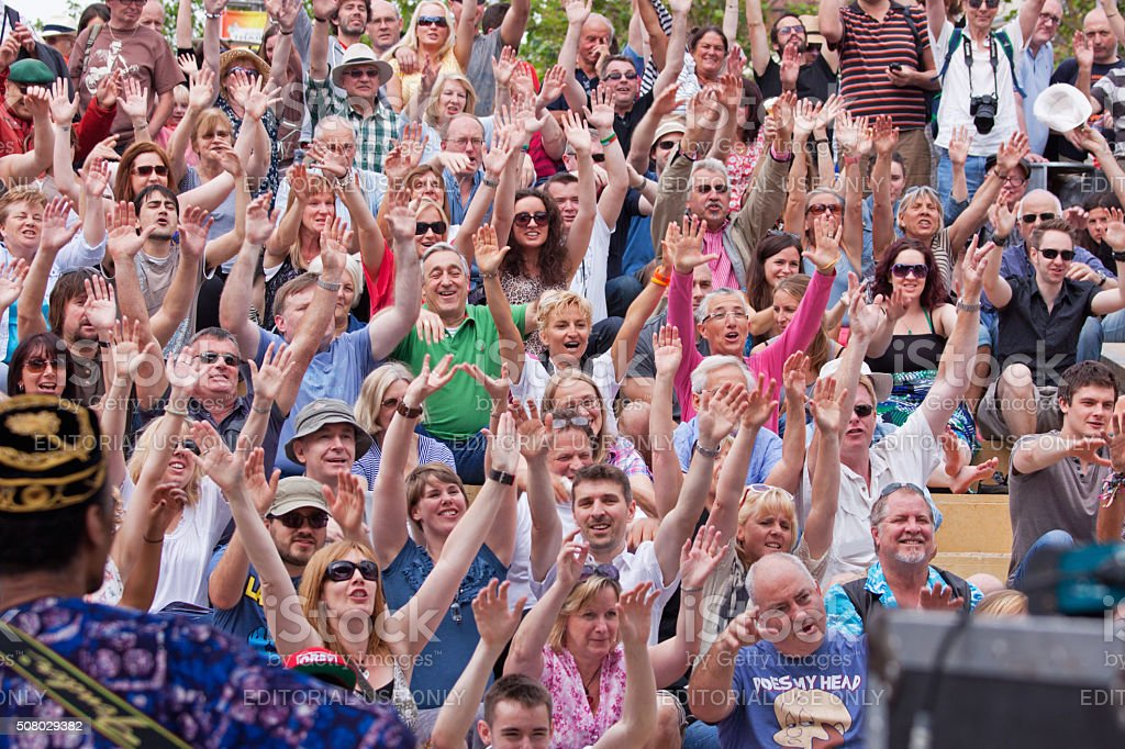 Happy audience with arms aloft at a free festival UK stock photo