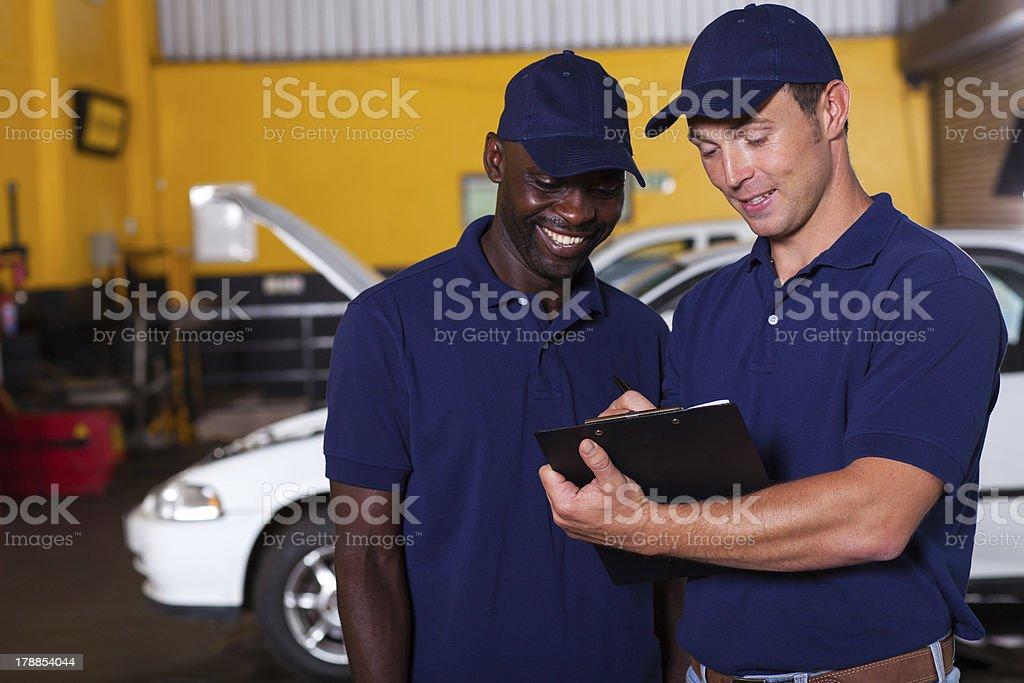 happy auto mechanics going through checklist royalty-free stock photo