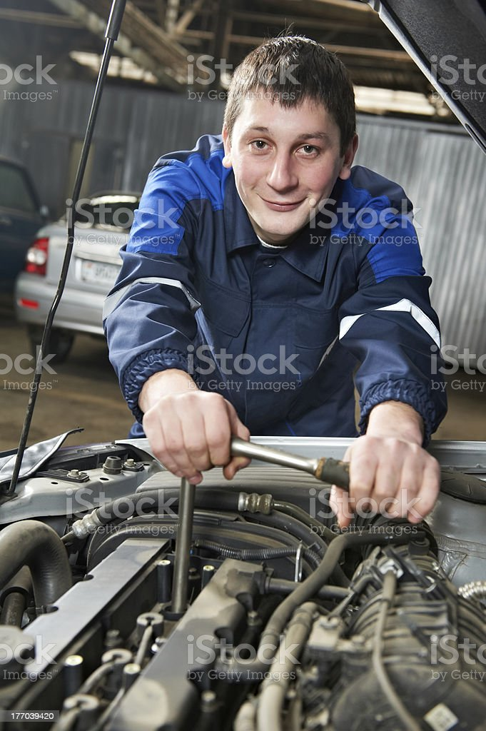 happy automotive mechanic at work with wrench royalty-free stock photo