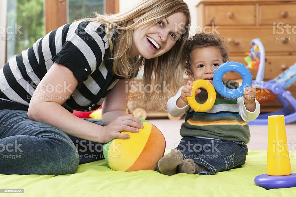 Happy Baby And Childmider Enjoying Playtime stock photo
