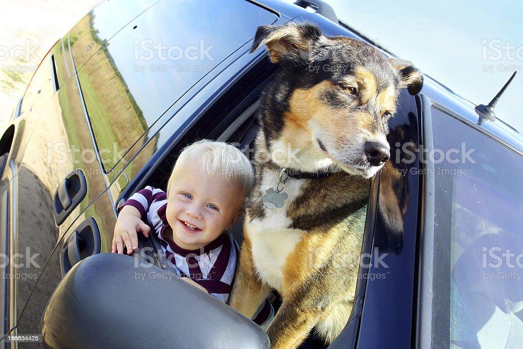 Happy Baby and Dog in Minivan Window stock photo