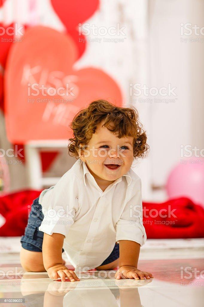 Happy baby boy crawling on floor stock photo
