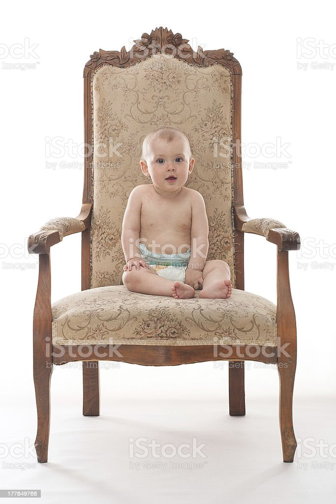 Happy baby boy sits on an antique arm chair royalty-free stock photo