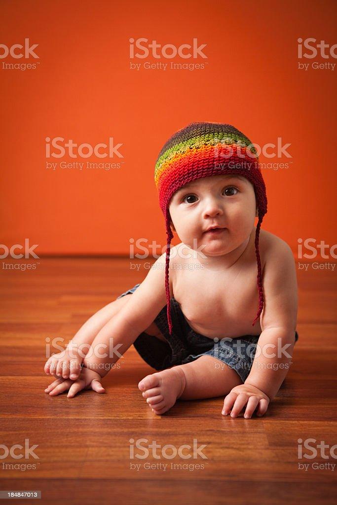 Happy Baby Boy Wearing Beanie Cap, Sitting On Hardwood Floor royalty-free stock photo