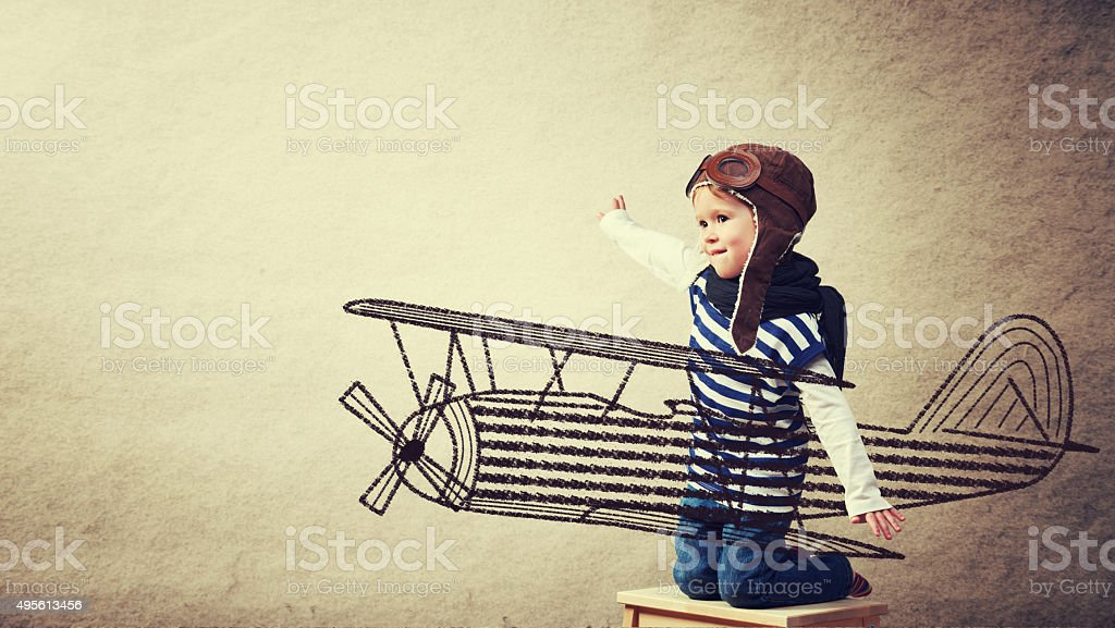 Happy baby dreams of becoming a pilot aviator stock photo