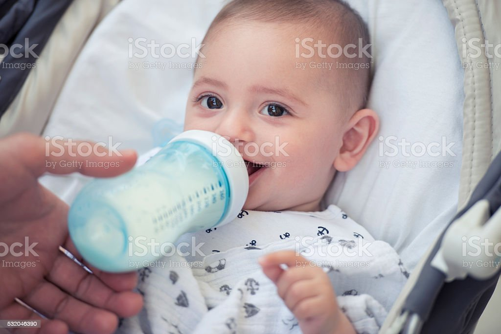 Happy baby drinking milk from bottle. stock photo