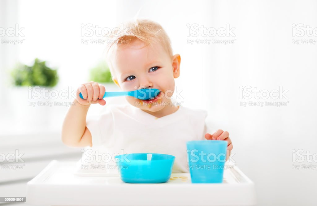 Happy baby eating himself stock photo
