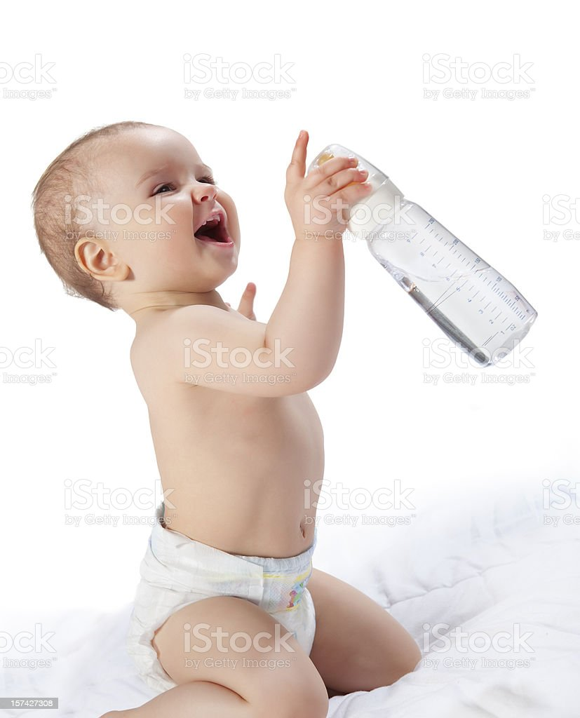 Happy baby girl holding a feeding bottle in bed stock photo