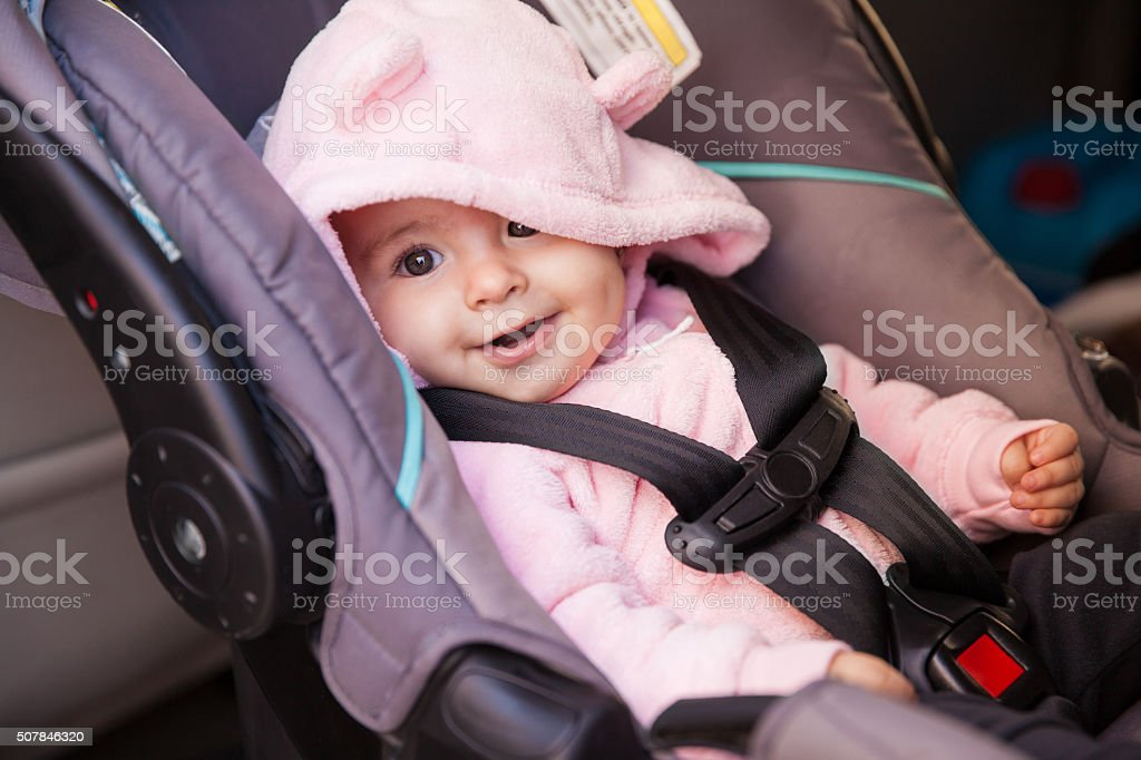 Happy baby girl in a car seat stock photo