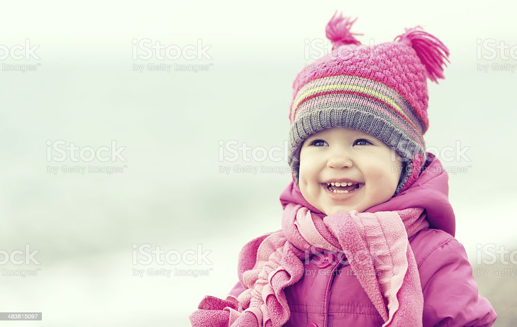 Happy baby girl in a pink hat and scarf stock photo