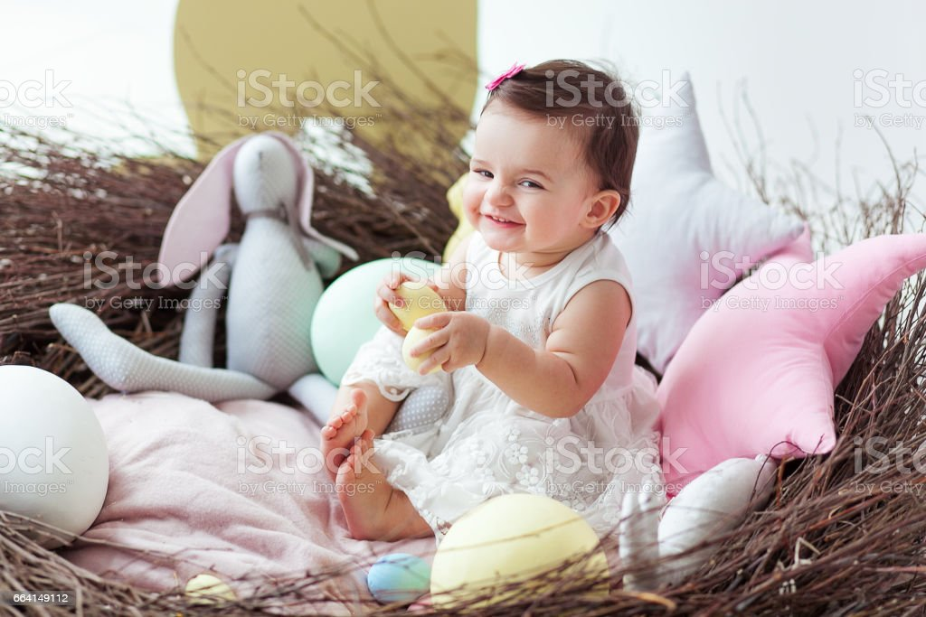 Happy baby girl in big Easter nest with eggs. Easter holiday concept: nest with baby hare stock photo