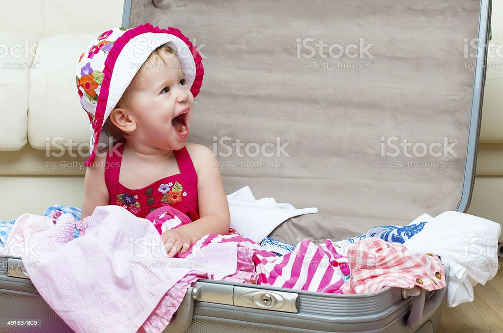 happy baby girl is going on trip, pack suitcase royalty-free stock photo