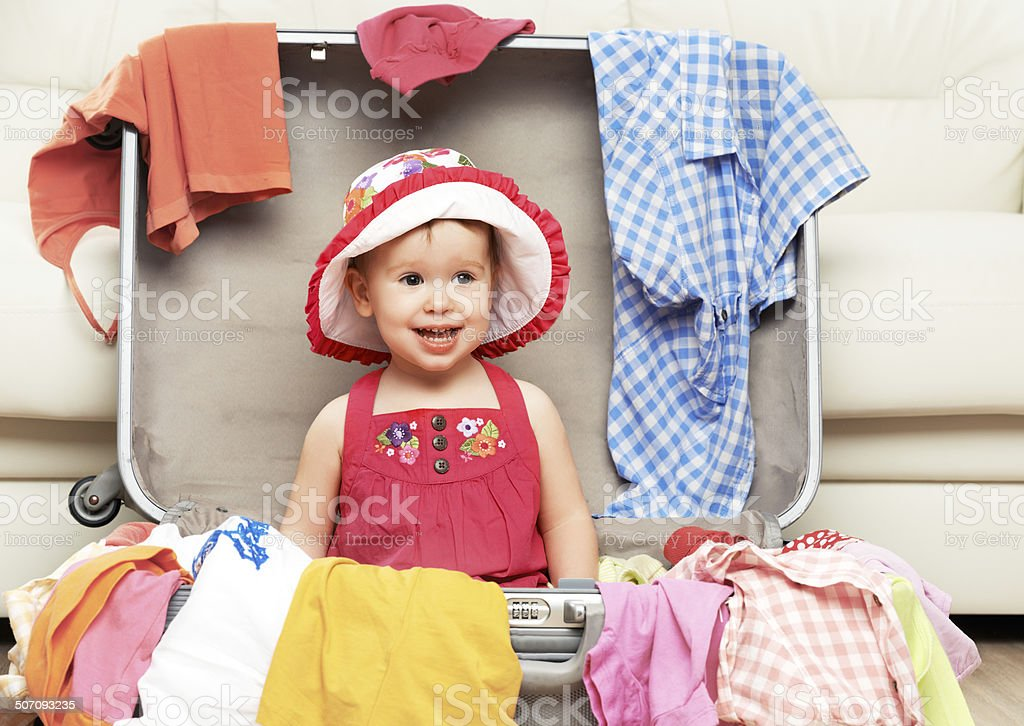 happy baby girl is going on trip, pack suitcase stock photo