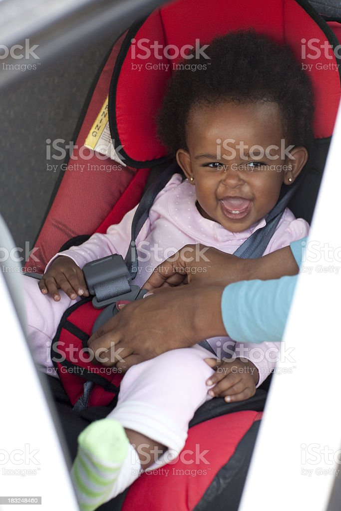 Happy baby girl  on a safety car  seat. royalty-free stock photo