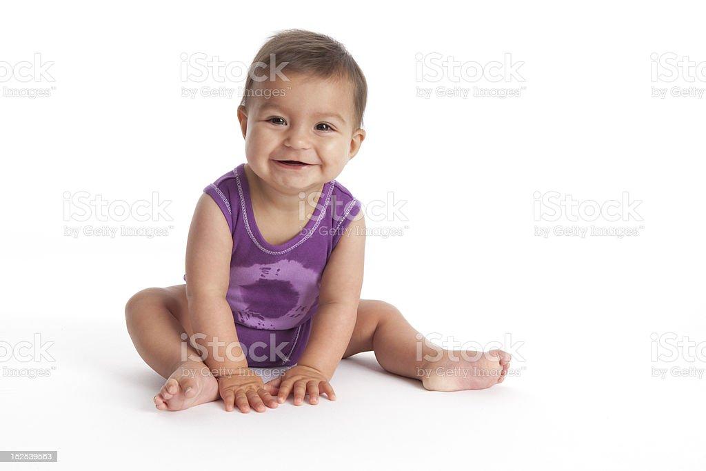Happy Baby girl sitting on the floor stock photo