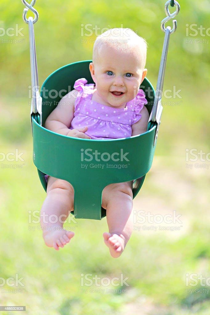 Happy Baby Girl Swinging at Playground stock photo