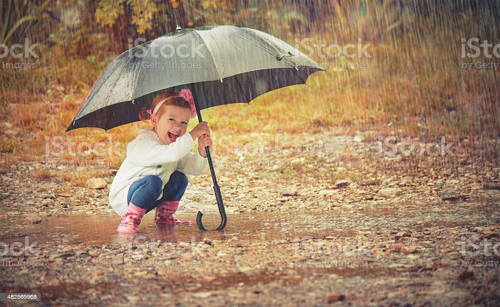 happy baby girl with an umbrella in rain on nature stock photo