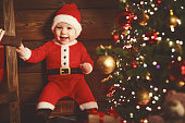 Happy baby in a Christmas costume Santa Claus